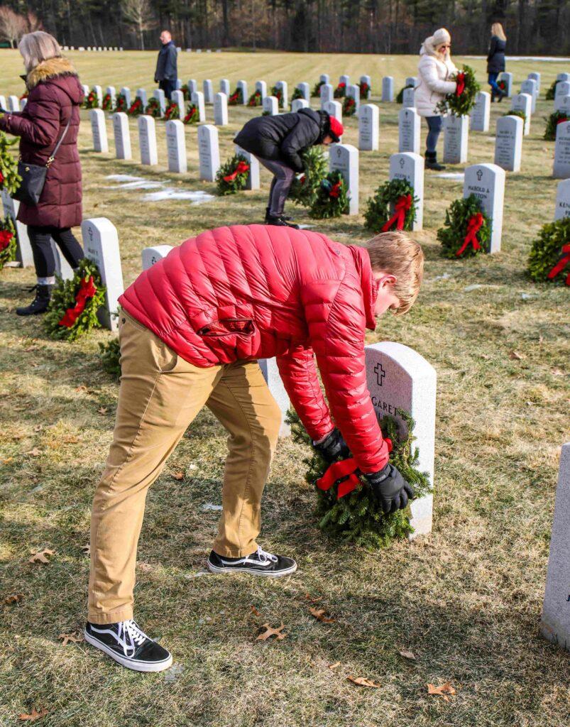 Wreaths-across-America Student placing wreath in Massachusetts Veterans' Cemetery